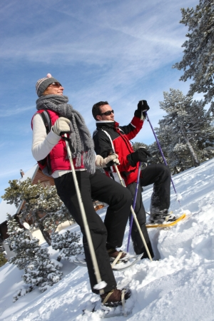 active couple snow shoeing outdoors