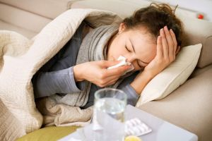 Young woman sick with allergies lying on sofa