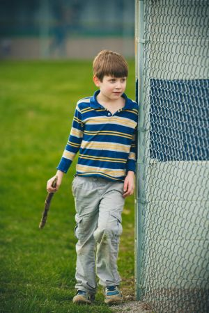 young boy standing next to a fence
