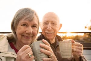 An older couple drinks from mugs.