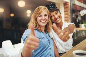 "two young women giving a ""thumbs up"" and smiling"