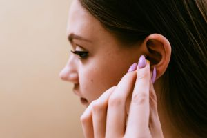 A woman puts in earplugs.