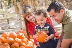 Couple with young child at pumpkin patch in fall