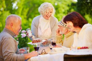 Two mature couples laughing at birthday celebration outdoors