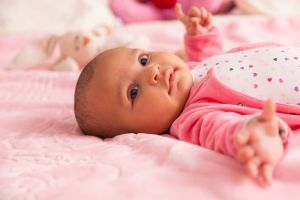 Cute newborn baby dressed in pink laying in crib