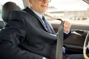 businessman in car fastening seat belt