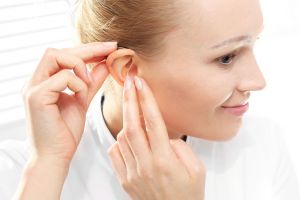 A woman inserts her hearing aid.