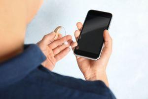 Une aide auditive et un smartphone tenus par un homme.