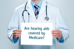 Doctor holds a sign asking if hearing aids are covered by Medicare.