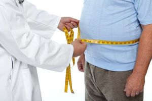 Physician in white lab coat measure waist of heavy man