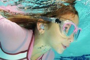 A girl swims underwater with ear plugs.