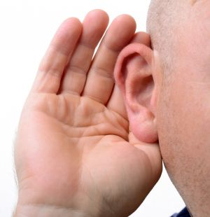 Close up of man's ear with hand cupped behind it