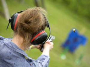 woman at shooting range wearing hearing protection earmuffs
