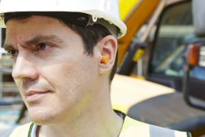 Man wearing hard hat and earplugs at construction site
