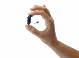 close up of hand holding attractive small hearing aid