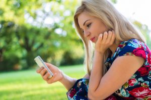 Young woman browsing online dating site on mobile phone outdoors