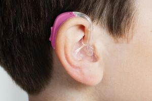 close-up on bright pink pediatric hearing aid on a child's ear