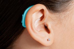 close-up on bright blue pediatric hearing aid on a child's ear