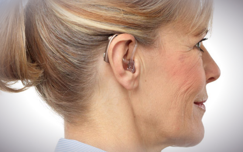 A woman wearing an Oticon Dynamo power hearing aid