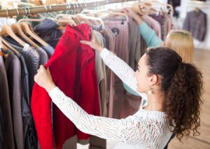 female shopper selecting a jacket from rack