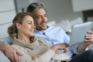 Happy mature couple lounging on sofa with tablet