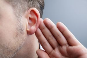 A man holds his ear.