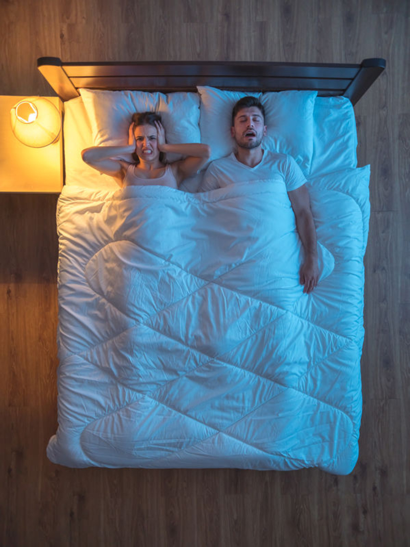 A woman indicates frustration at her snoring bed partner.