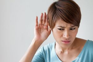 A woman tries to hear out of one ear.