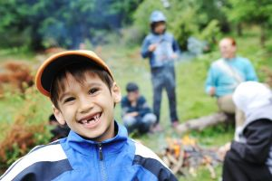 Young boy smiling with summer camp bonfire in background