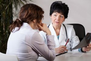 Woman consulting doctor wearing white coat