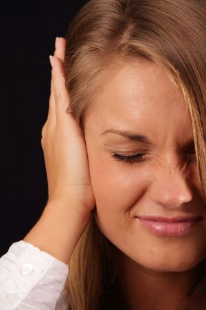Woman holding ear as if trying to silence tinnitus
