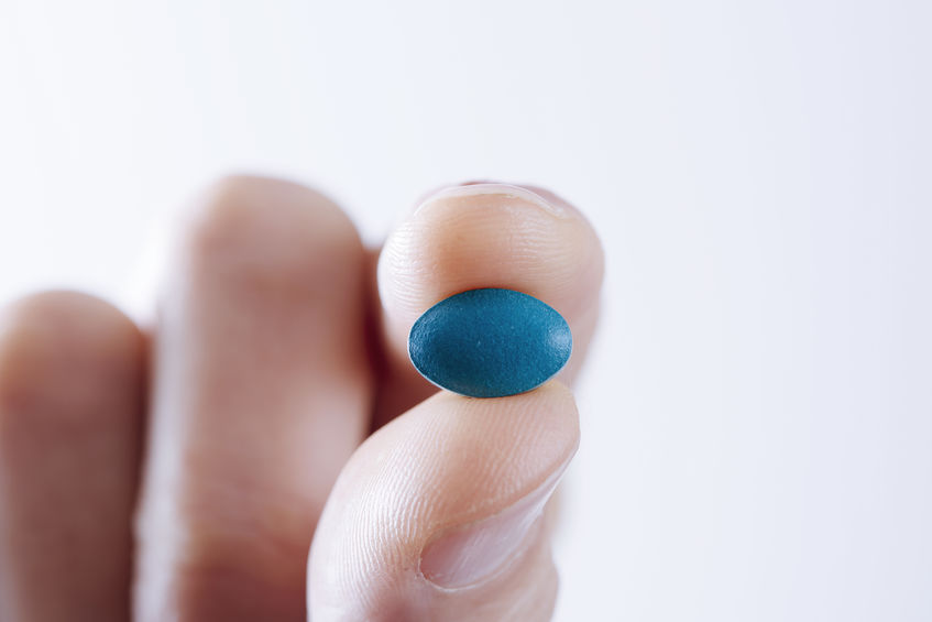 A man holds a Viagra tablet.