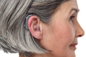 A woman wears a hearing aid with an earmold.