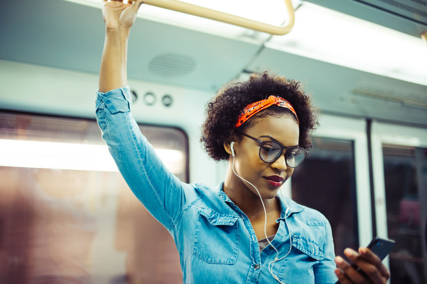 A woman on a subway train listens to music via earbuds.