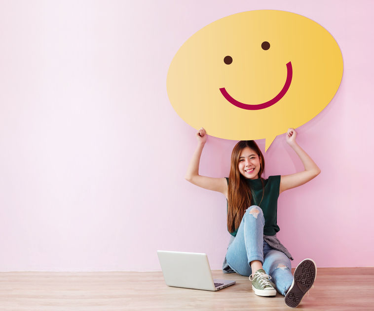 Woman holding smiley face