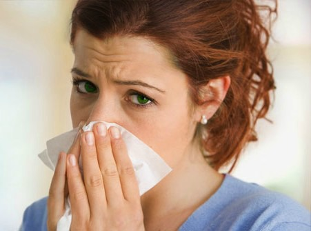 Woman With Tissue Over Mouth and Nose