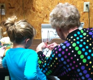 Grandma and child bent over a sewing machine together
