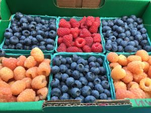 close-up on 6 boxes of raspberries and blueberries