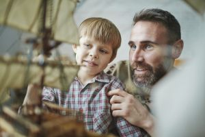 father and young son building model ship