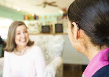 A woman with a hearing aid talks to a friend.