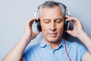 Man listening to headphones with eyes closed