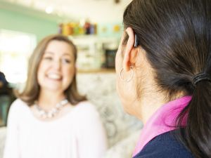 A woman wearing a hearing aid talks happily to a friend.