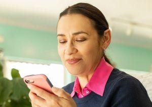 Une femme parle sur son smartphone tout en portant un appareil auditif.