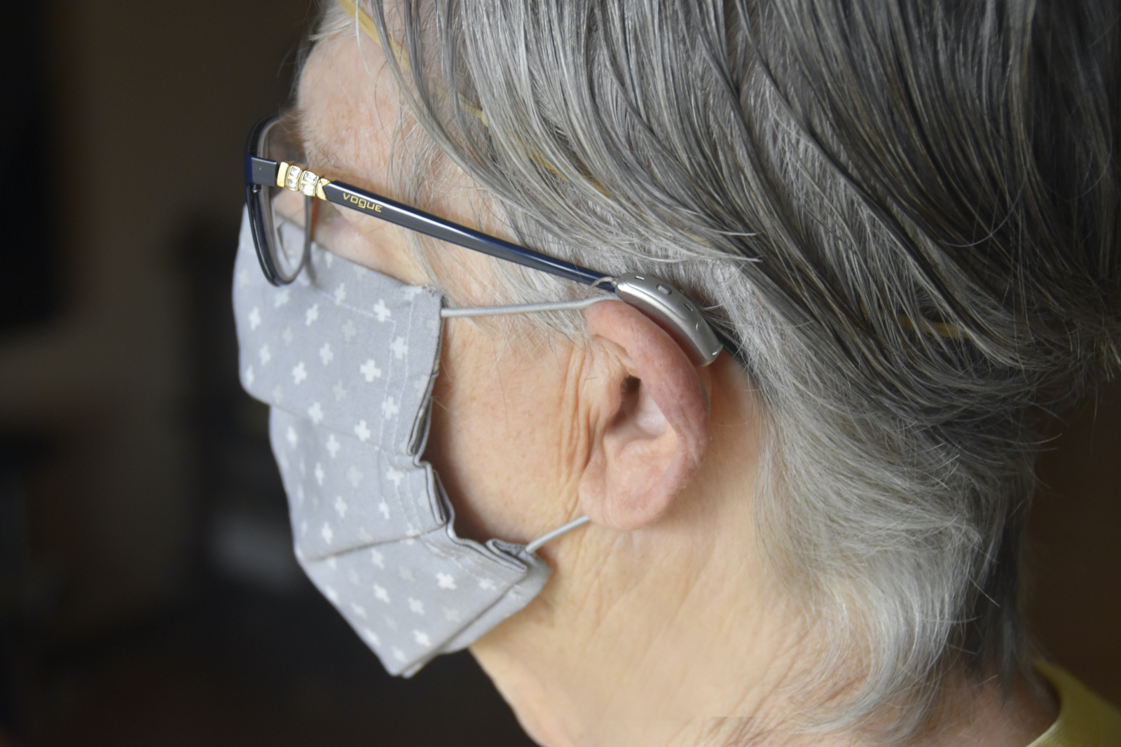 Woman wearing a face mask, hearing aids and eyeglasses.