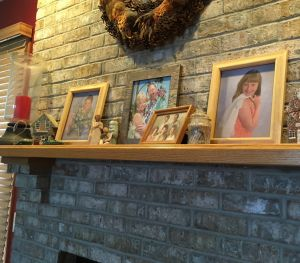 Line up of family photographs on a fireplace mantle