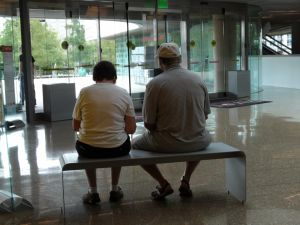 An older couple sits on a bench at the museum