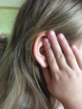 child holding her hand over her ear