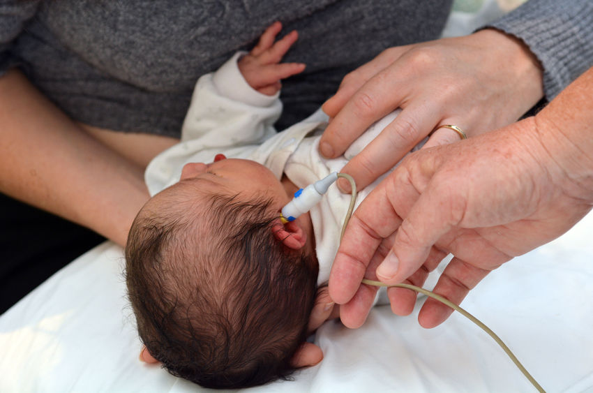 A newborn receives hearing screening in the hospital.