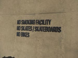 No smoking, biking or skateboarding sign on a building