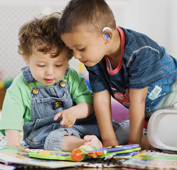 toddlers wearing hearing aids playing together
